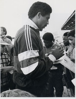 Daley Thompson signing autographs at the reopening of the Terence McMillan Stadium. 1985.