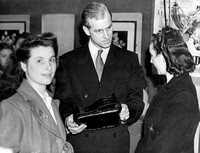 The Duke of Edinburgh examines a handbag made by girls of the leatherwork and millinery club during a visit to the Dockland Settlement. 1947.